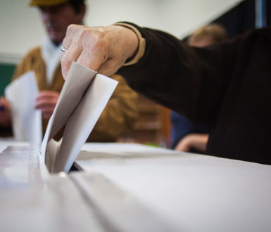 Person Posting Their Vote In A Ballot Box